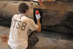 NTSB investigator examining fracture surfaces.