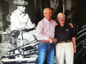 Lenny Sadler (left), and Ed Malzahn in front of a mural in the Wichita, KS, dealership.